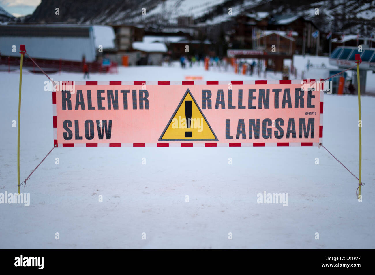 Slow sign on piste in Val D'Isere France. Close up of sign with background out of focus. - Stock Image