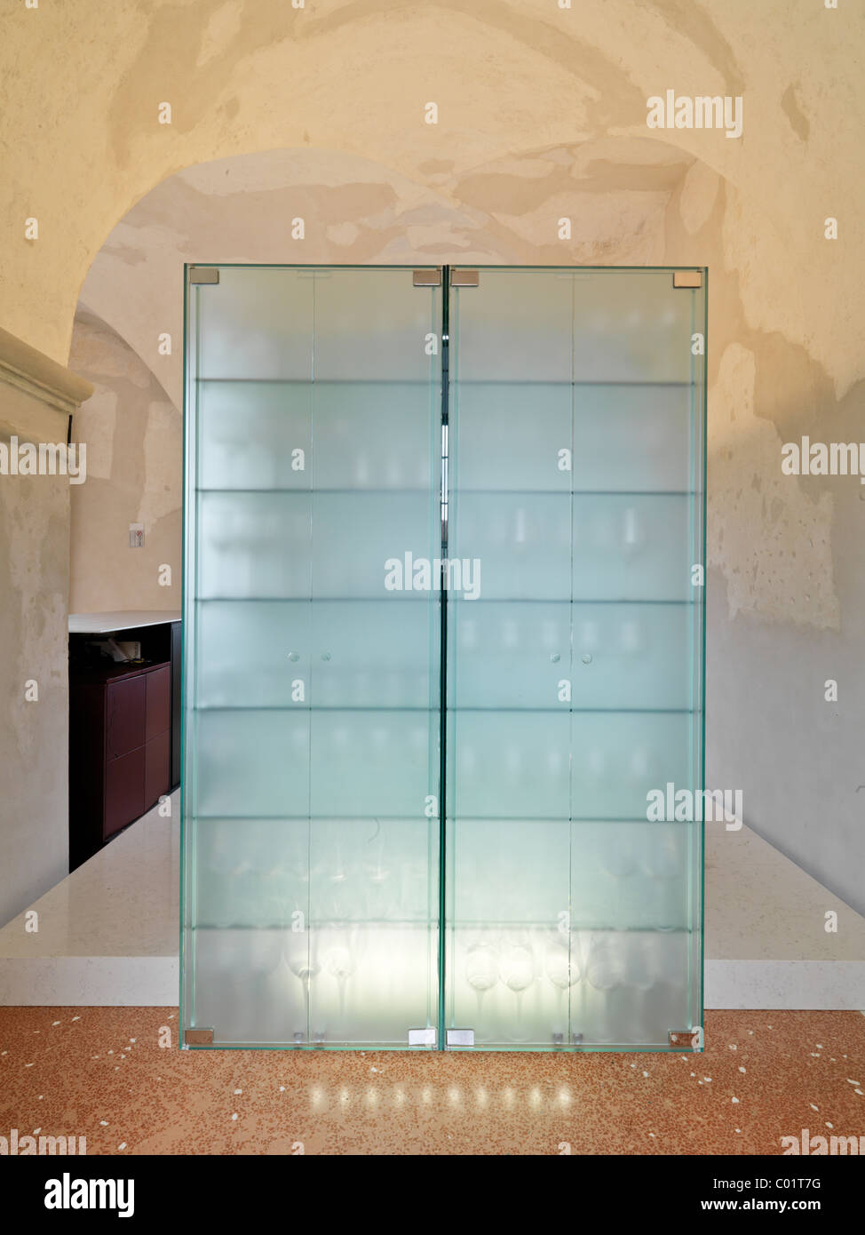 glass showcase in a bar inside a restaurant obtained by restoration of a  ancient building of the 15th century - Stock Image