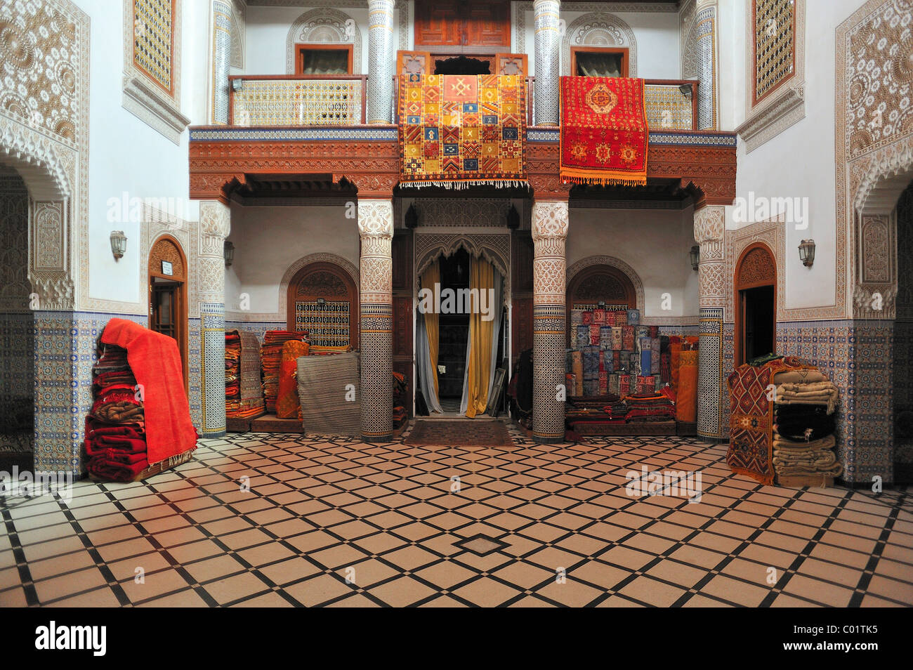 Carpets of a carpet dealer, displayed for sale in an old Riyadh, palace courtyard, Marrakech, Morocco, Africa - Stock Image
