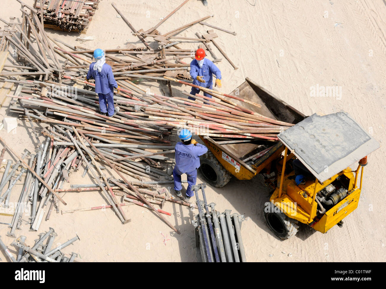 Construction workers sorting scaffolding poles, Dubai, United Arab Emirates, Middle East - Stock Image