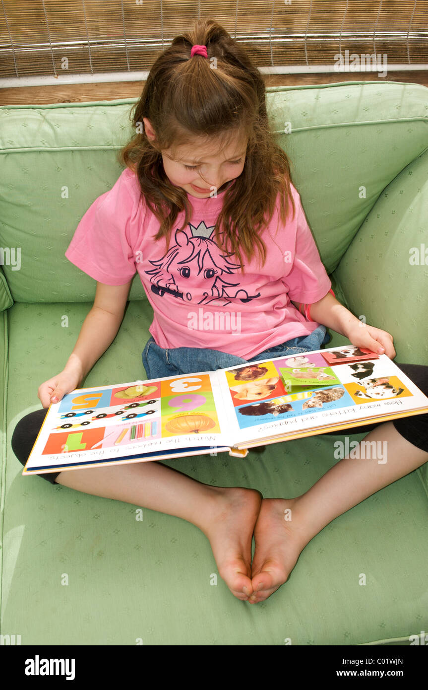 6-year old girl who is a sufferer of Dyslexia looking at a words and pictures book - Stock Image