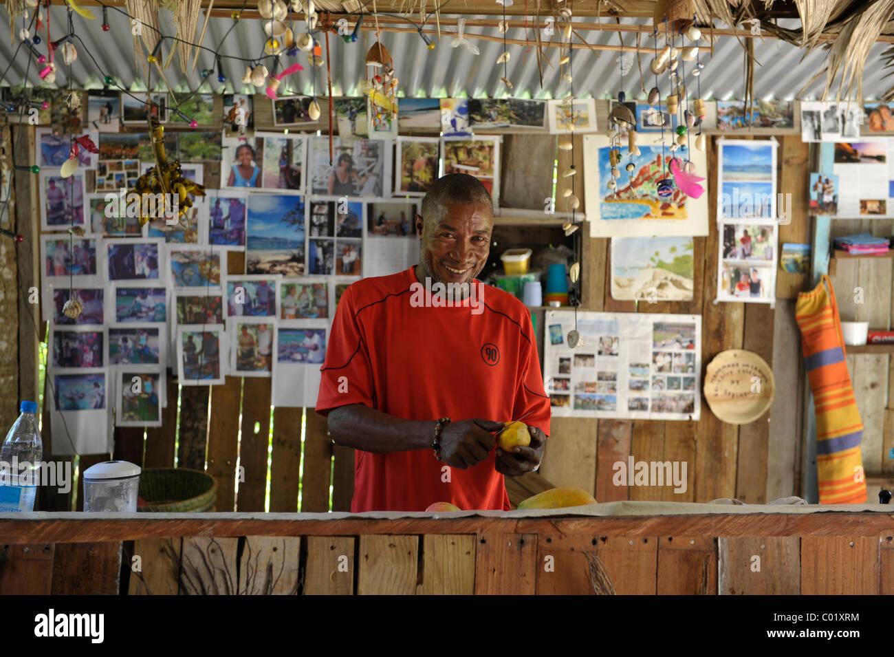 Smiling dark skinned man at beach bar, La Digue, Seychelles - Stock Image