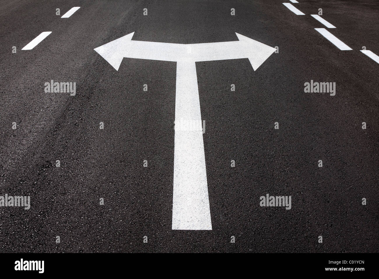 Left and right turn arrows painted on tarmac roadway. Concept for turning, decision, choice, which way, right, left. - Stock Image
