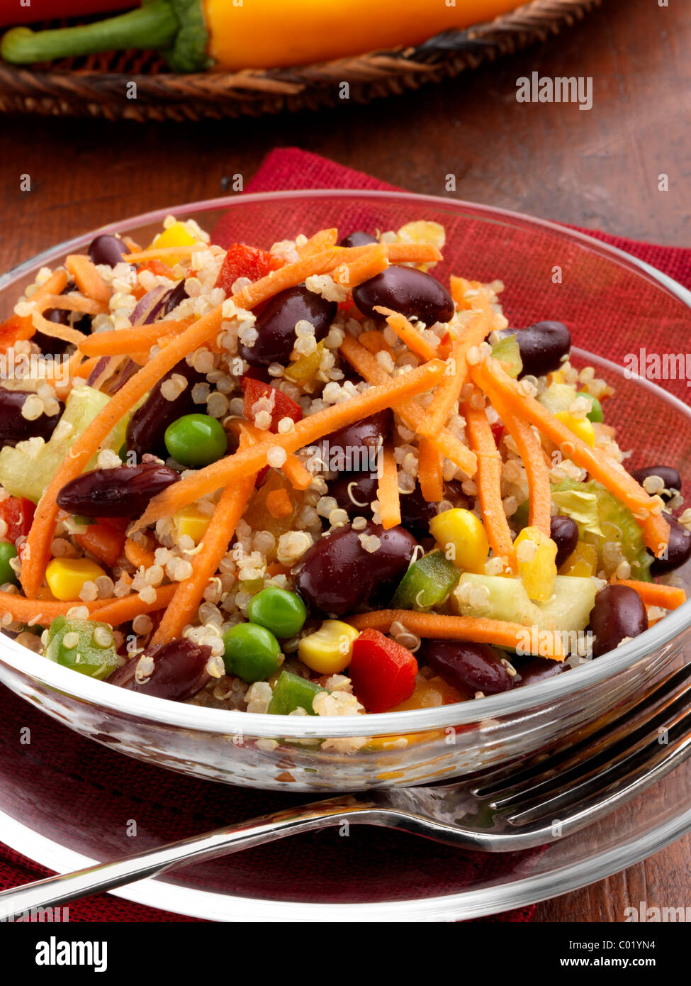 Individual portion of quinoa salad with peas sweetcorn carrots red peppers red kidney beans vegetarian meal - Stock Image