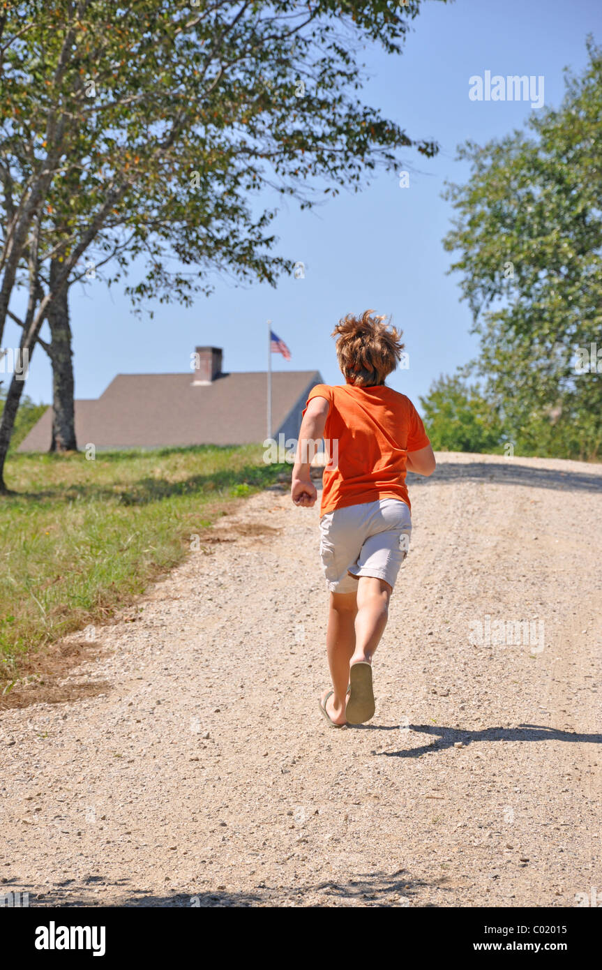 12 year old boy running up hill to house - Stock Image