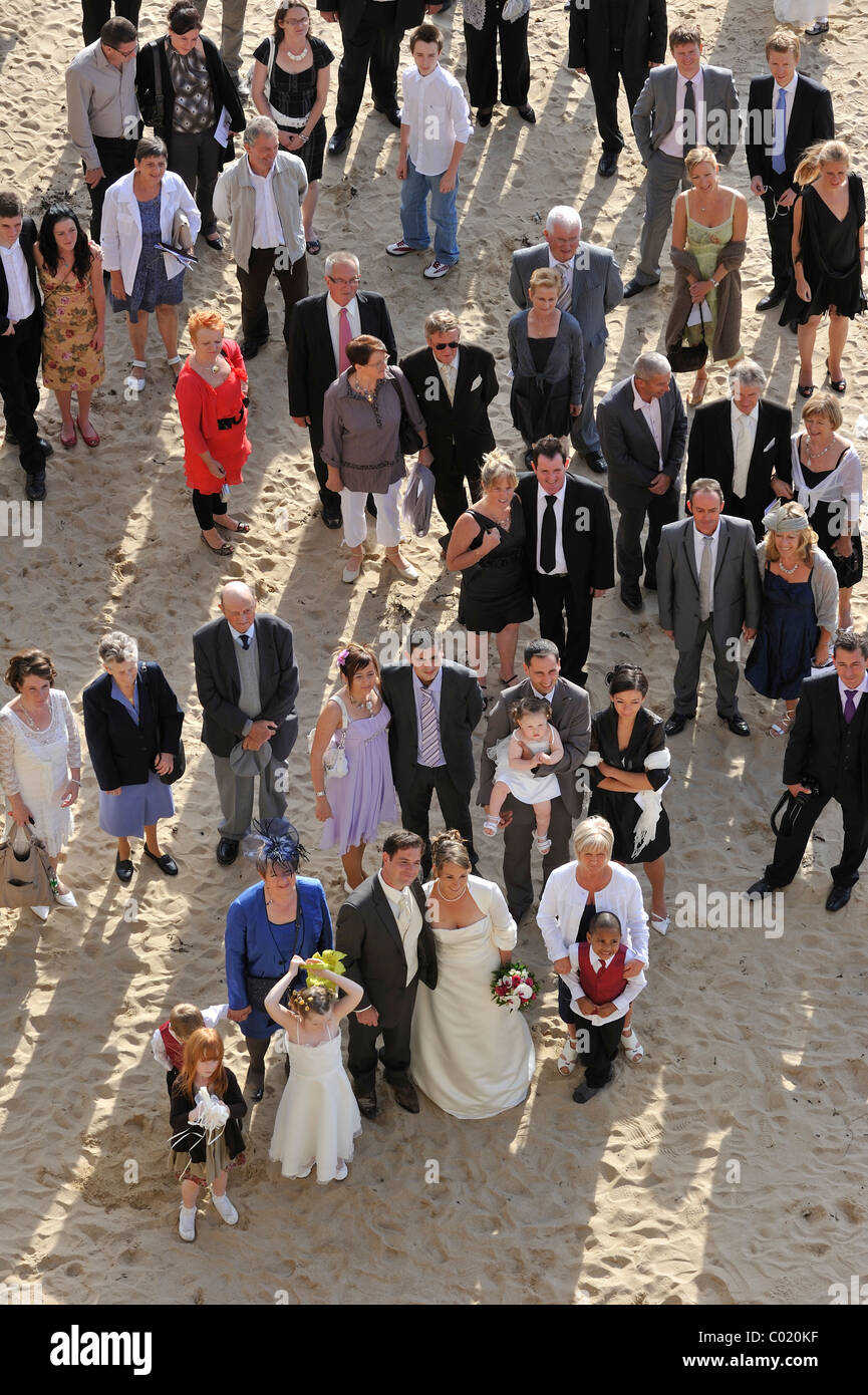 Bride, groom and guests on beach at wedding party - Stock Image