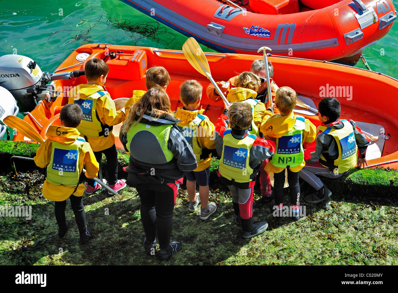 School children with life jackets boarding dinghy during sailing class - Stock Image