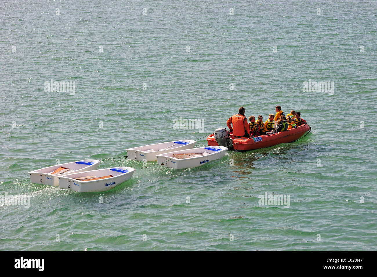 School children with life jackets in dinghy during sailing class - Stock Image