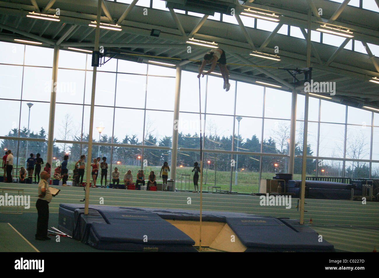 Athlete over the High Jump Bars at Lee Valley  Athletics Track, in Enfield, London. - Stock Image