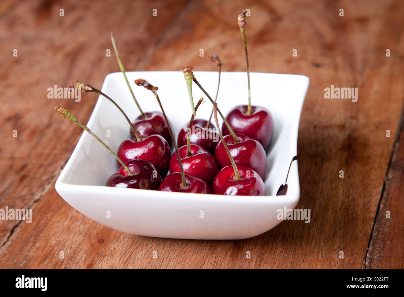 Cherries in bowl on wooden table - Stock Image