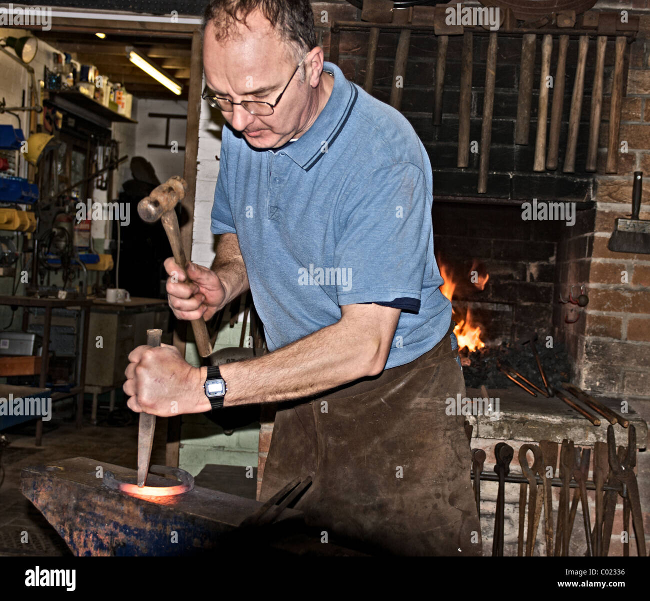 Blacksmith hammering a hole in the metal - Stock Image