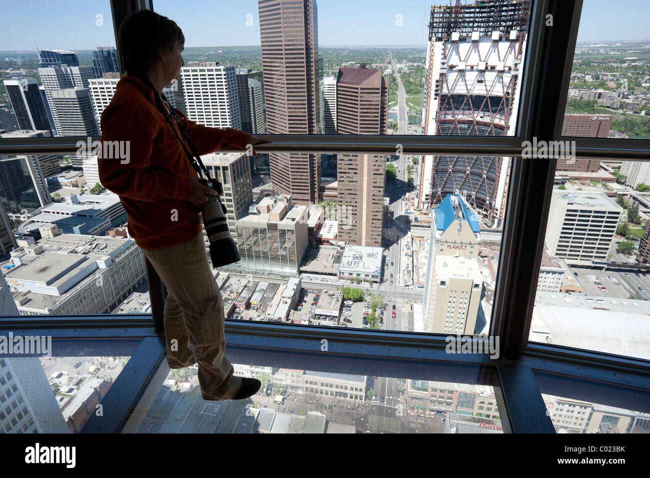 Female Standing On The Glass Floor Of The Observation Deck In The