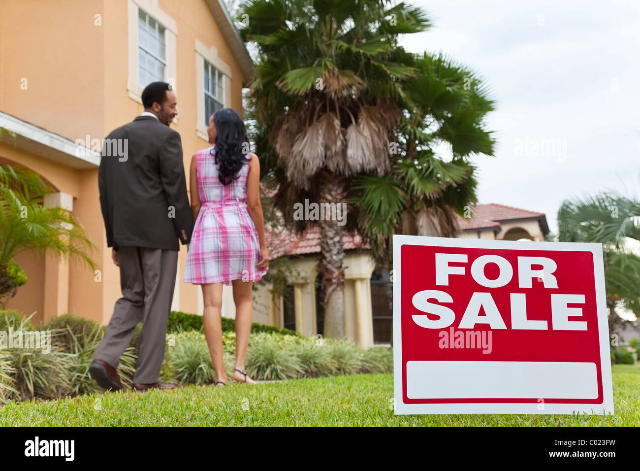 A happy African American man and woman couple house hunting outside a large house with a For Sale sign. - Stock Image