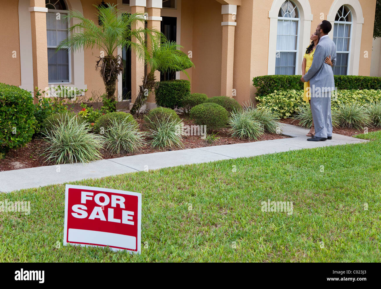 A happy African American man and woman couple house hunting outside a large house with a For Sale sign - Stock Image