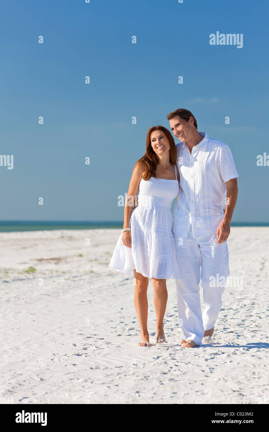 18a5a90a0629 Happy man and woman romantic couple in white clothes walking on a deserted  tropical beach with bright clear blue sky