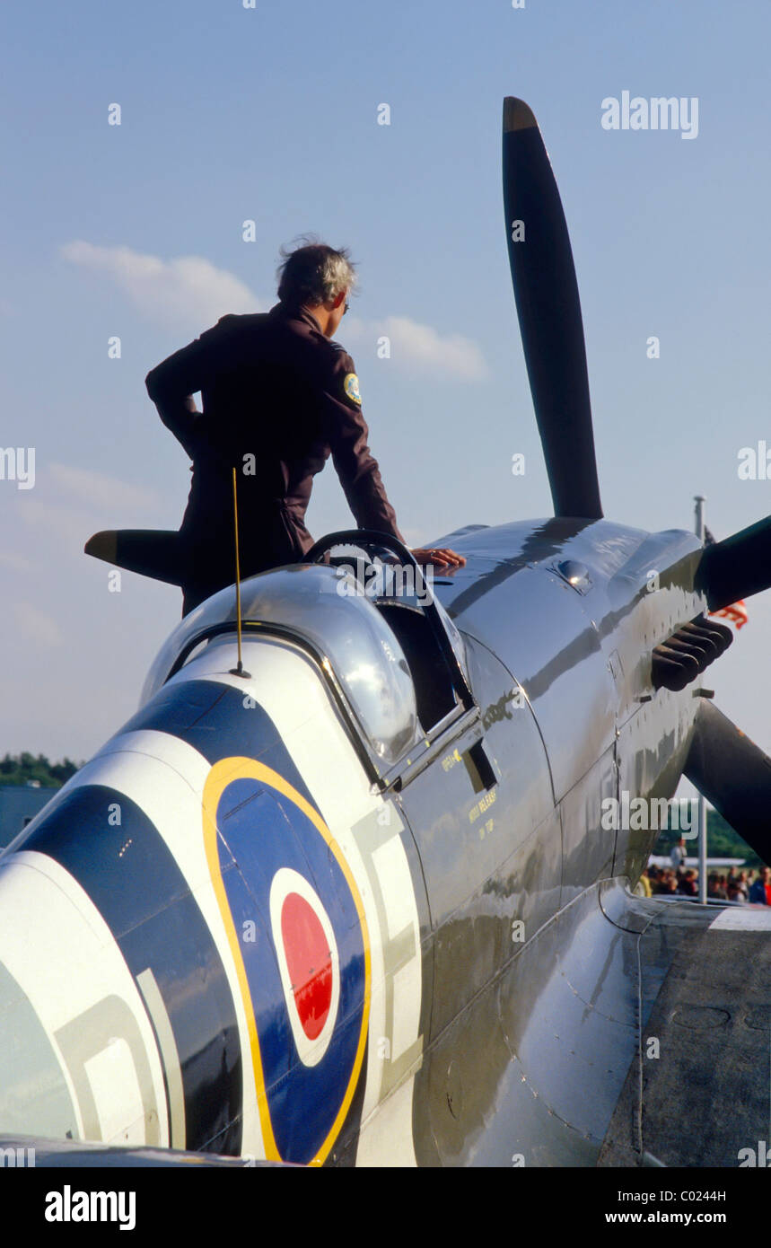 View of historical second world war Spitfire fighter plane RAF roundel on fuselage aircrew standing beside cockpit - Stock Image