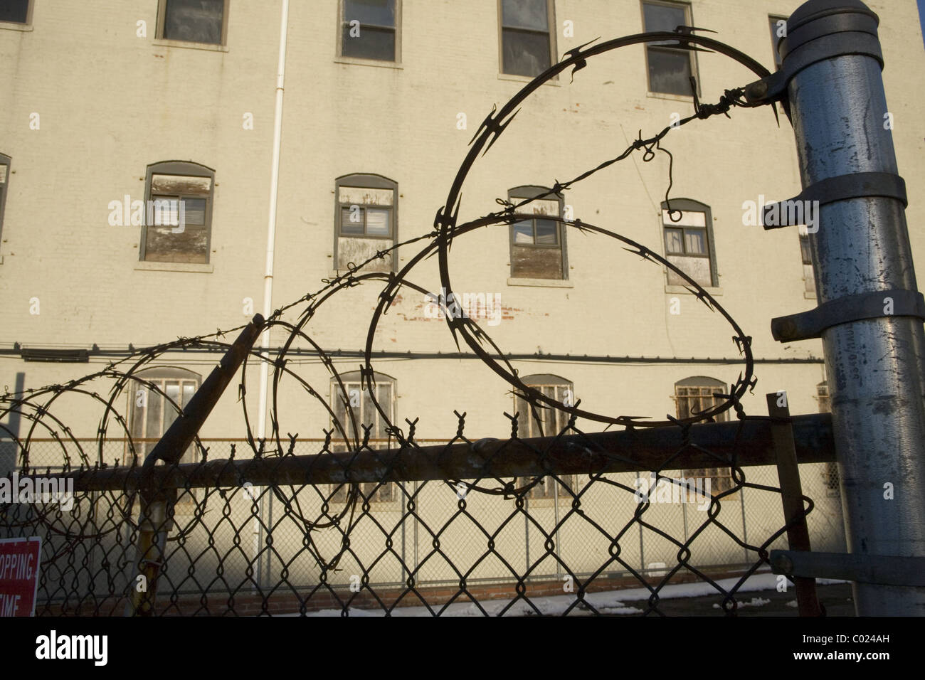 Barbed wire fence surrounding apartment building parking lot. - Stock Image
