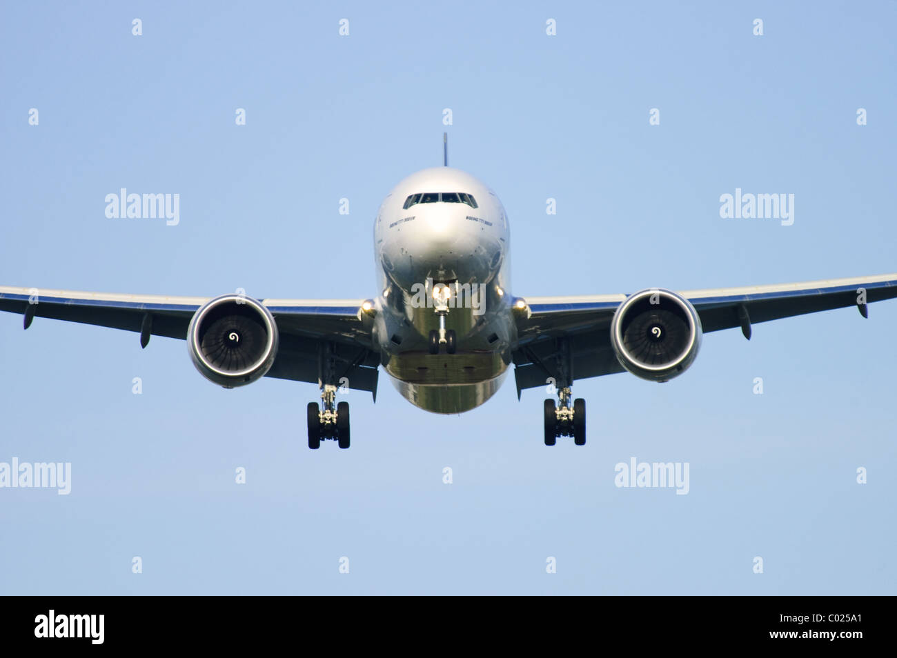 Heathrow runway approach by Boeing 777 plane seen head on on finals for landing at London Heathrow Airport, UK. - Stock Image