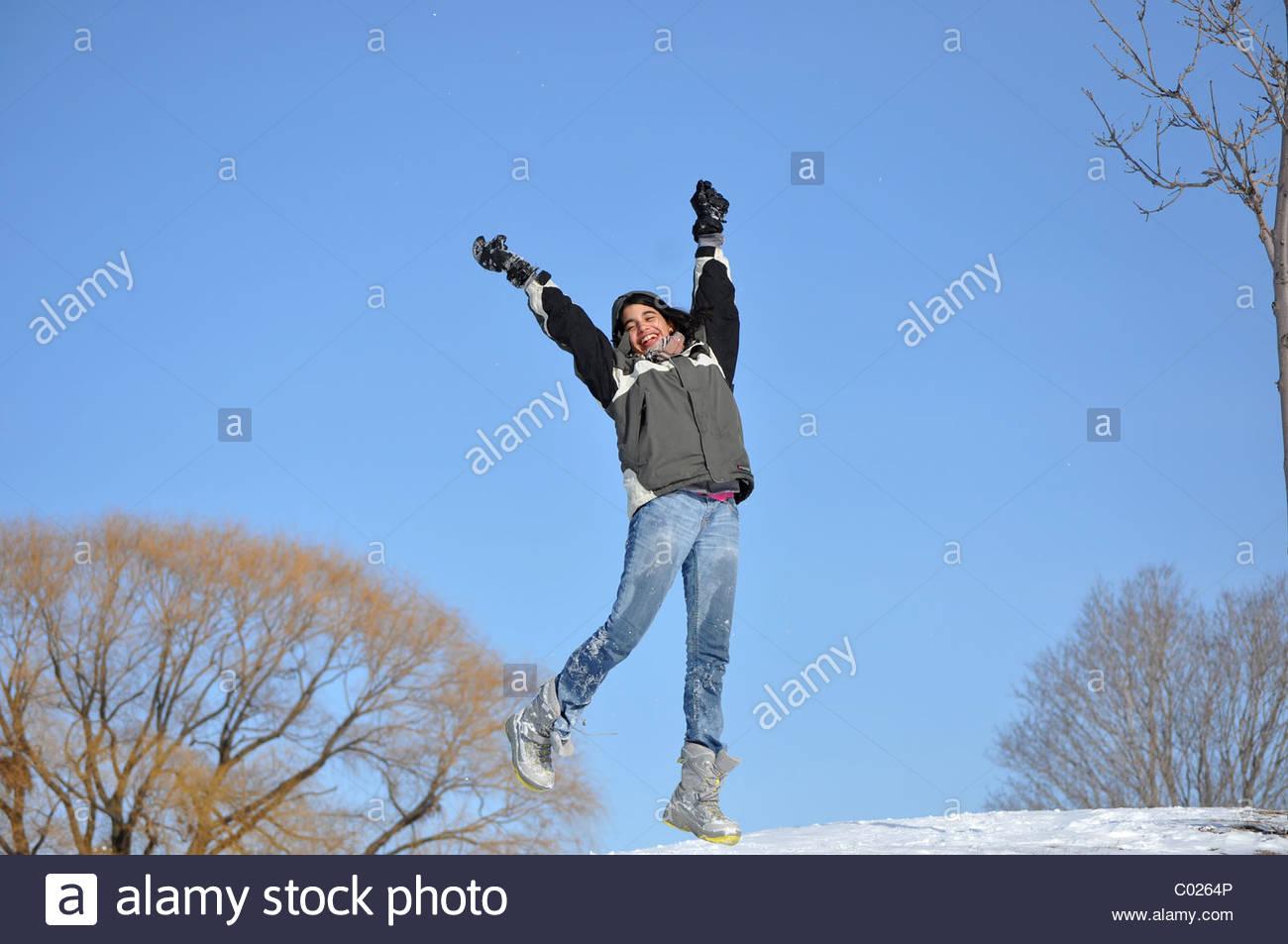 Hispanic immigrant family enjoying having fun in the first Winter snow - Stock Image