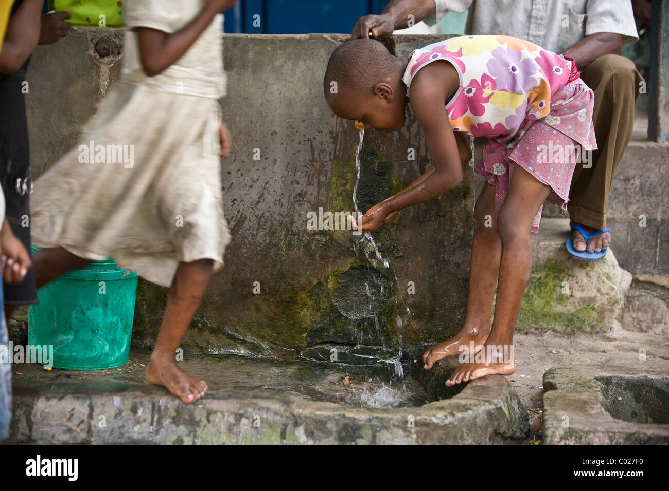 Children wash in a municipal water tap in Dar es Salaam, Tanzania, East Africa. - Stock Image