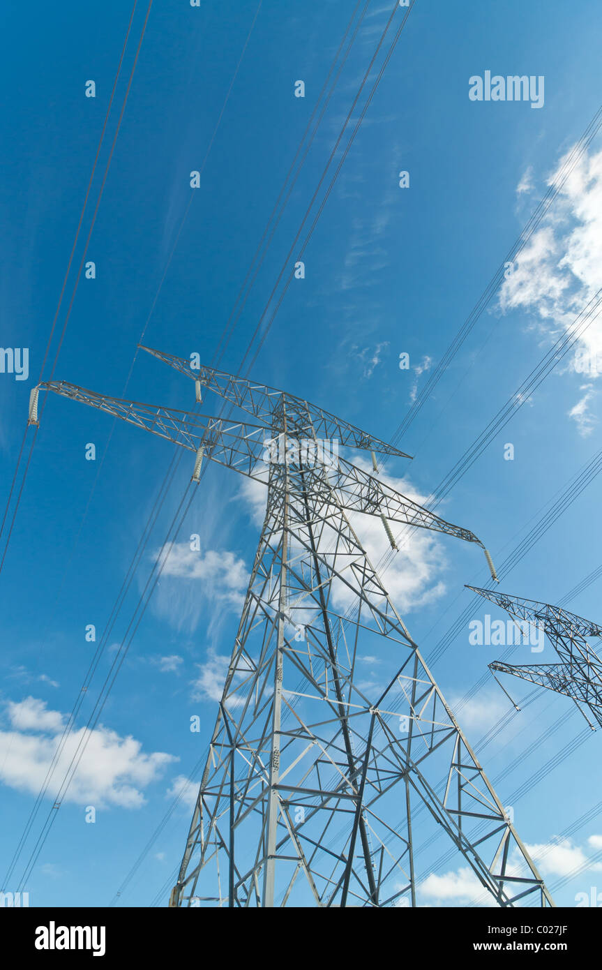 A pair of electrical transmission towers carrying high voltage lines. - Stock Image