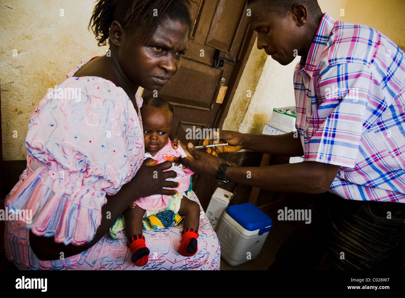 A health worker vaccinates a child against measles at the Binkolo community health center in Binkolo, Sierra Leone - Stock Image