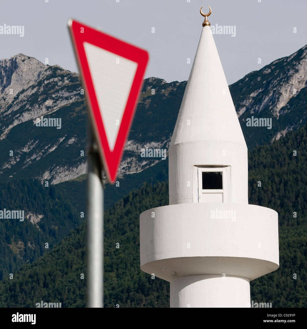 Yield-sign with minaret, controversial mosque in Telfs, Tyrol, Austria, Europe - Stock Image