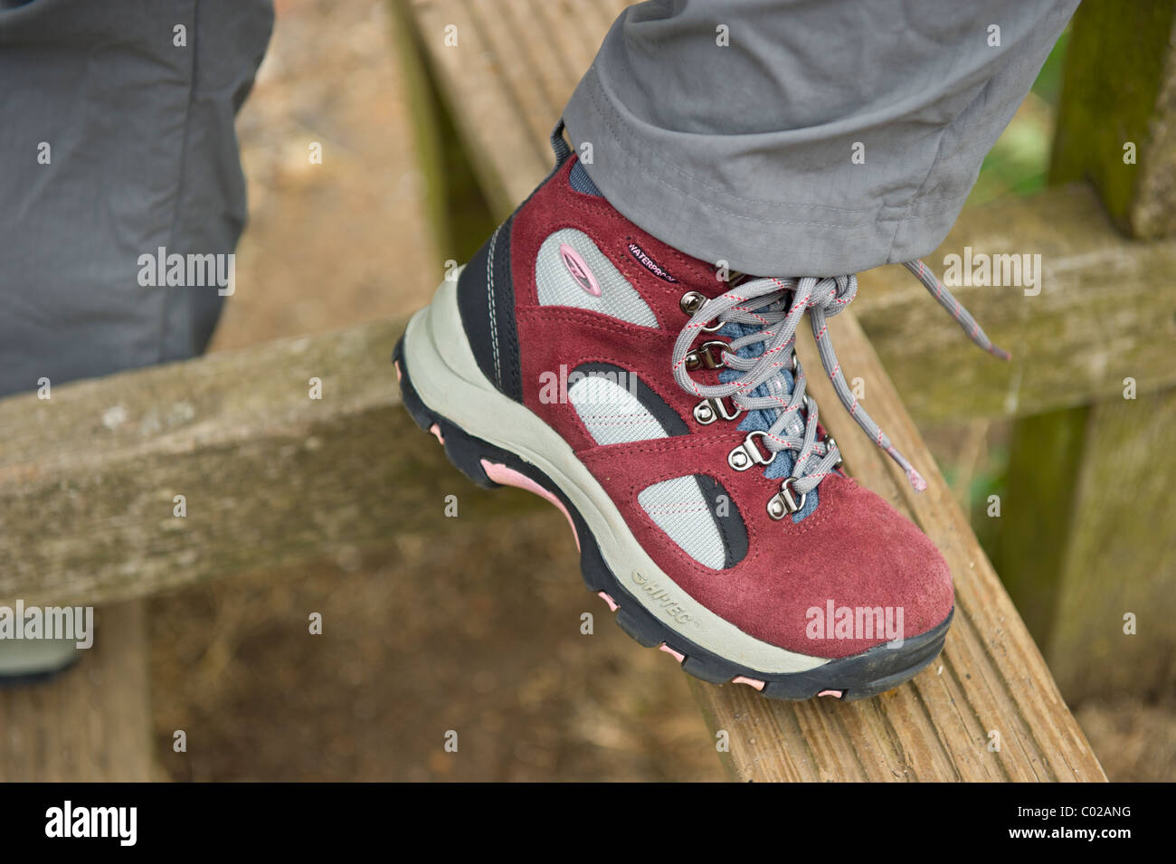 Close up image of young female walkers feet and boots while climbing over a style on a country walk in Hadleigh - Stock Image