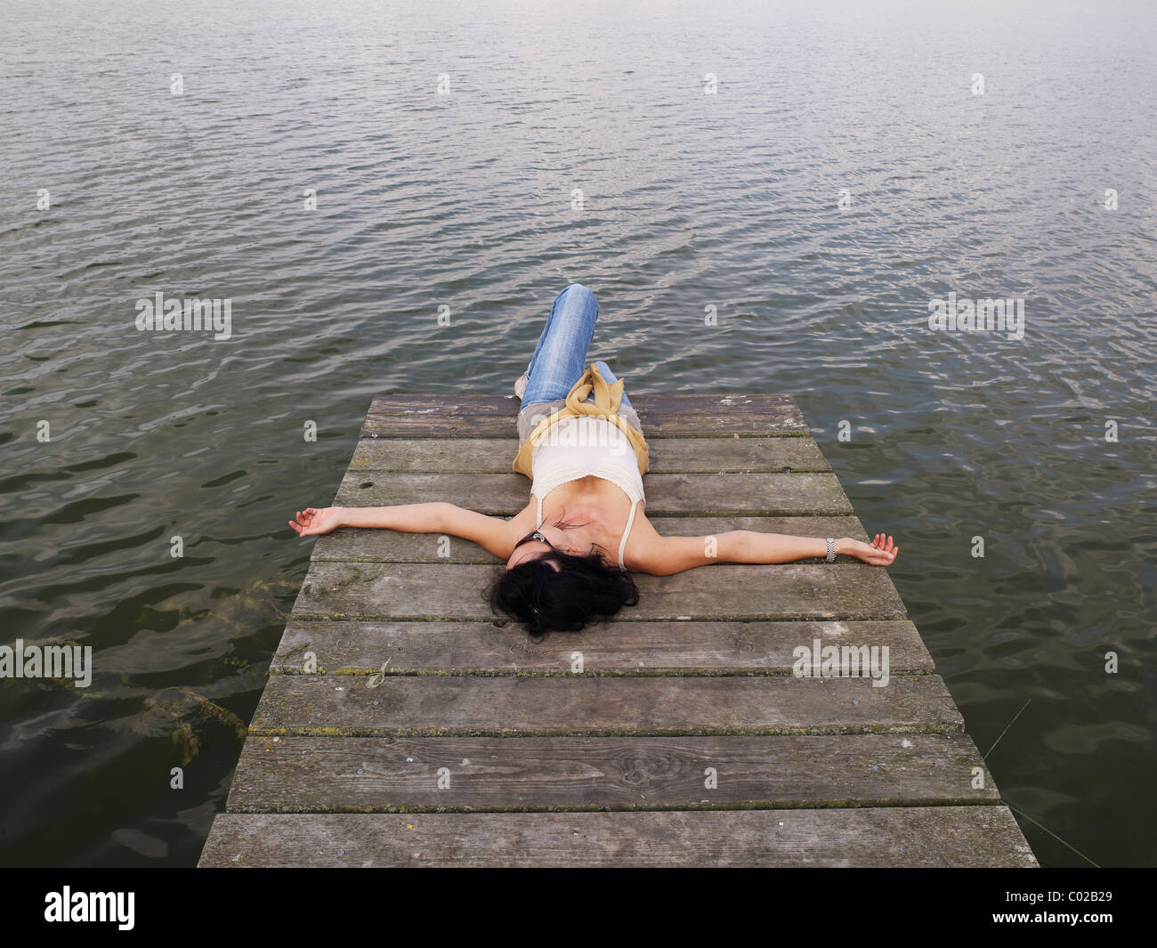 Woman relaxing lying on a wooden pier at a lake, Mecklenburg Lake District, Mecklenburg-Western Pomerania, Germany, - Stock Image