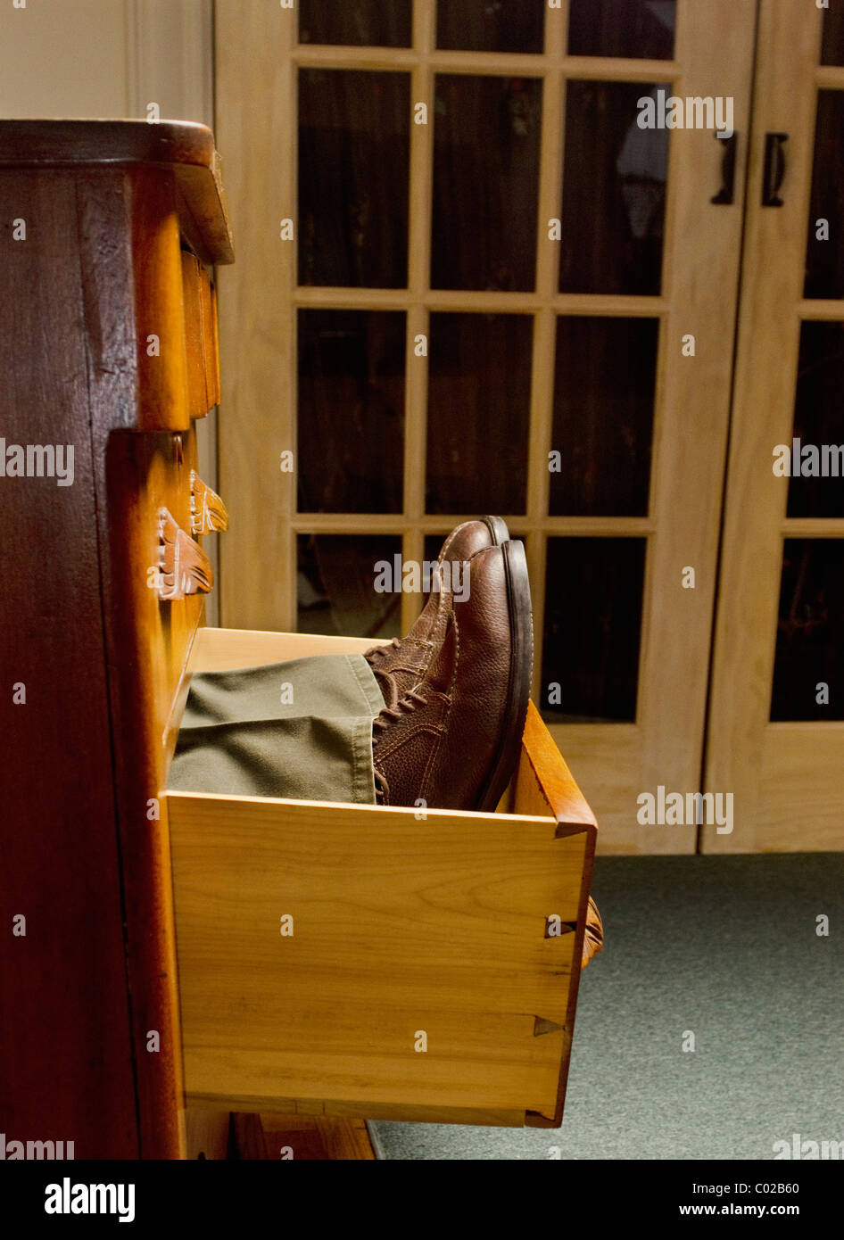 man's legs and shoes lying down in open dresser drawer - Stock Image