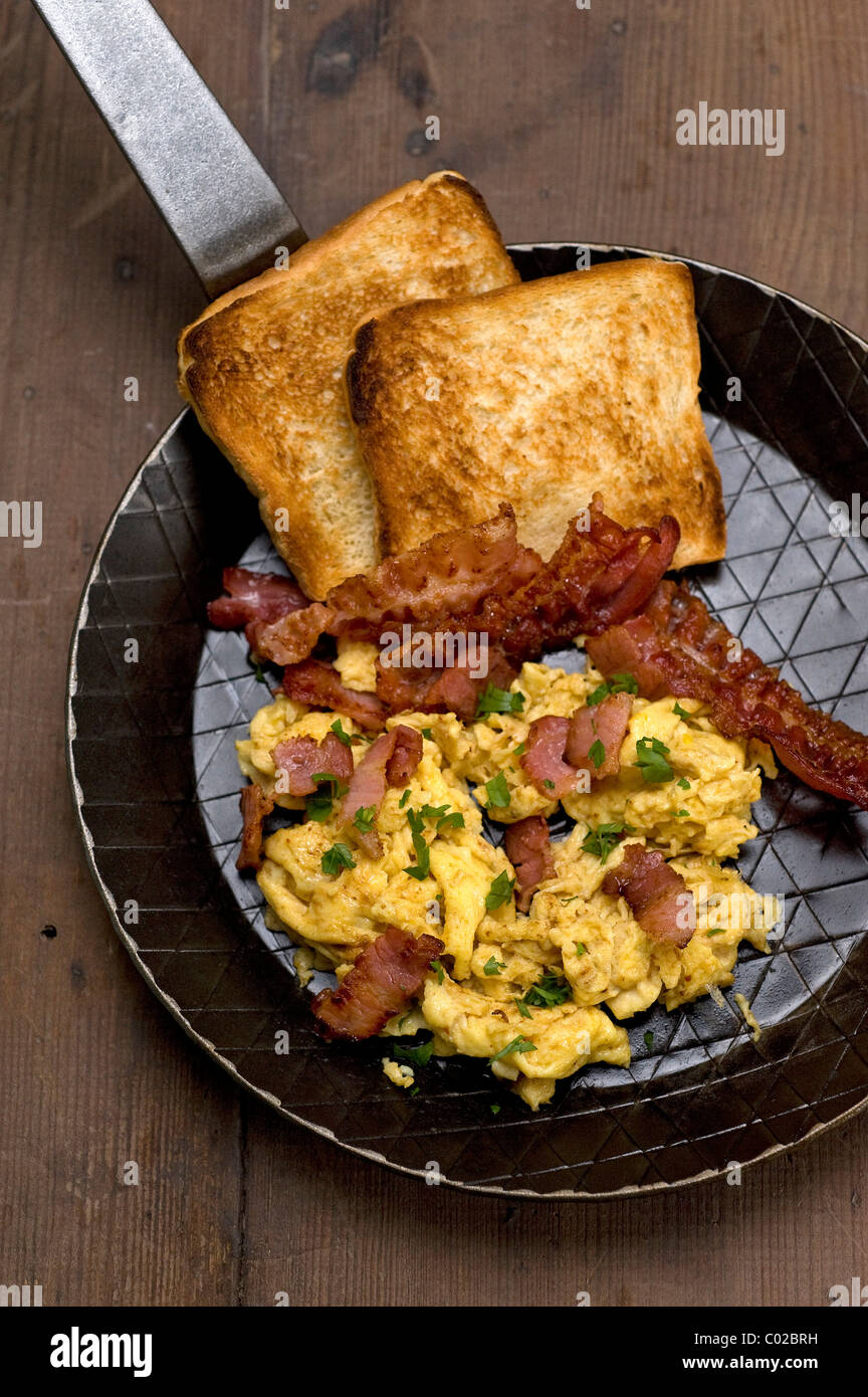 Scrambled eggs with fried bacon and toast - Stock Image