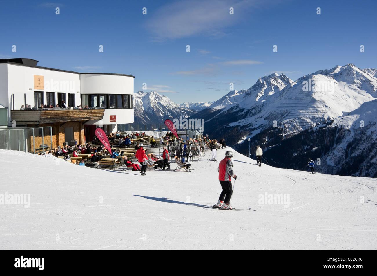 St Anton am Arleberg, Tyrol, Austria. Skiers on piste by Galzig gondola summit station with people sunbathing outside Stock Photo