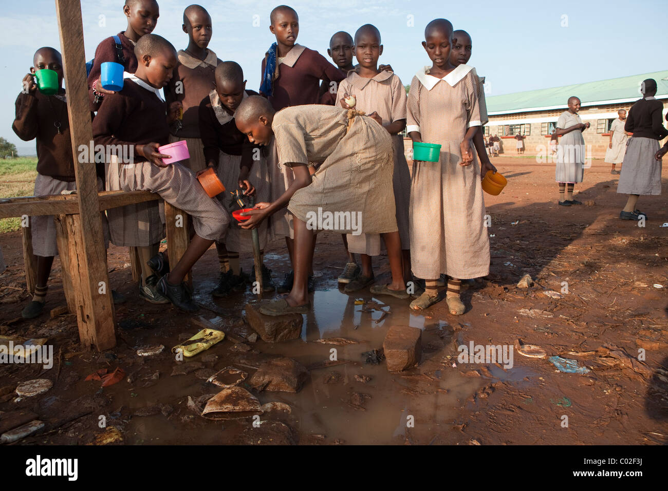 School children in Kenya draw water from a tap in Mosiro.  East Africa - Stock Image