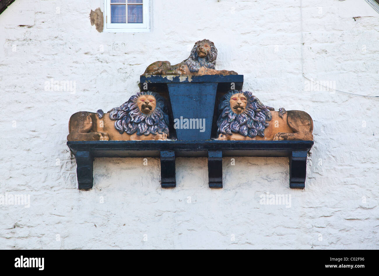 Three dimensional sign showing three lions on the wall of the former inn in the village of Holt, Wiltshire, England, - Stock Image