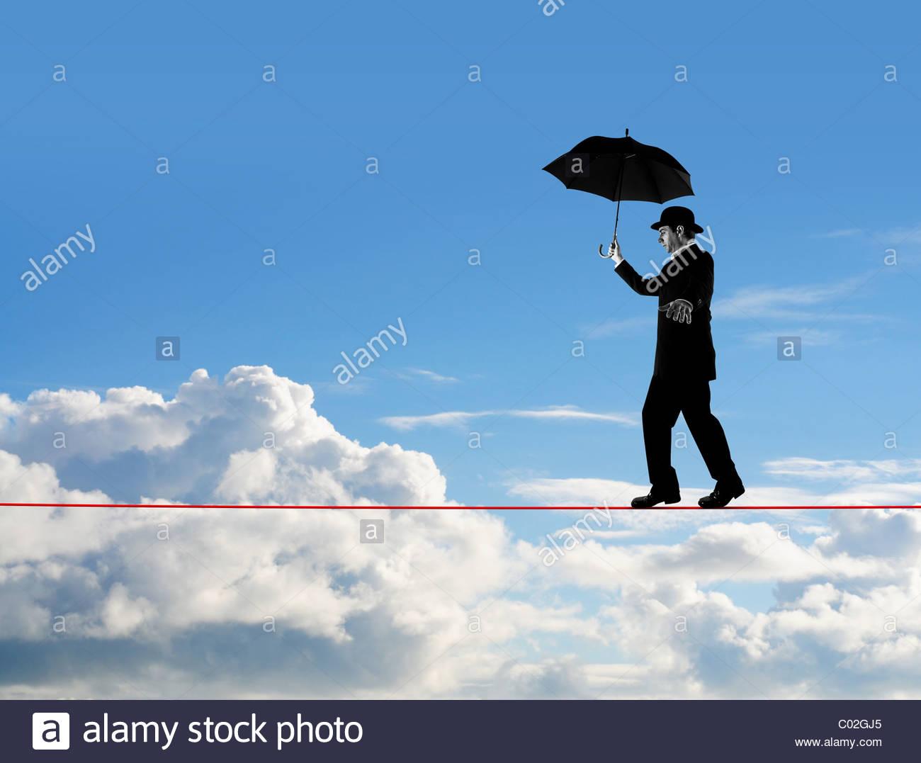 Man walking tightrope - Stock Image
