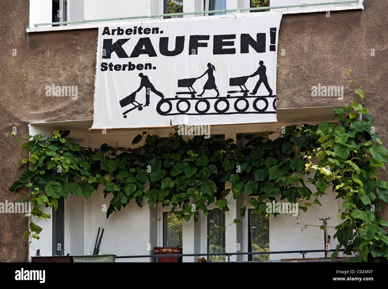 'Arbeiten kaufen sterben', German for 'work buy die', socio-critical banner on a house of former - Stock Image