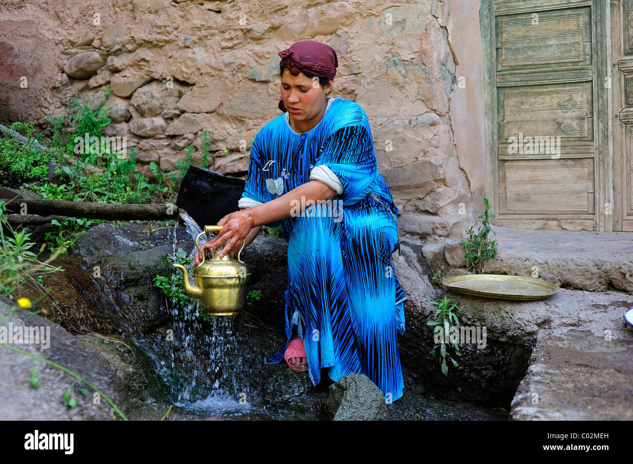 Woman cleaning a brass pot under running water, High Atlas, Morocco, Africa - Stock Image