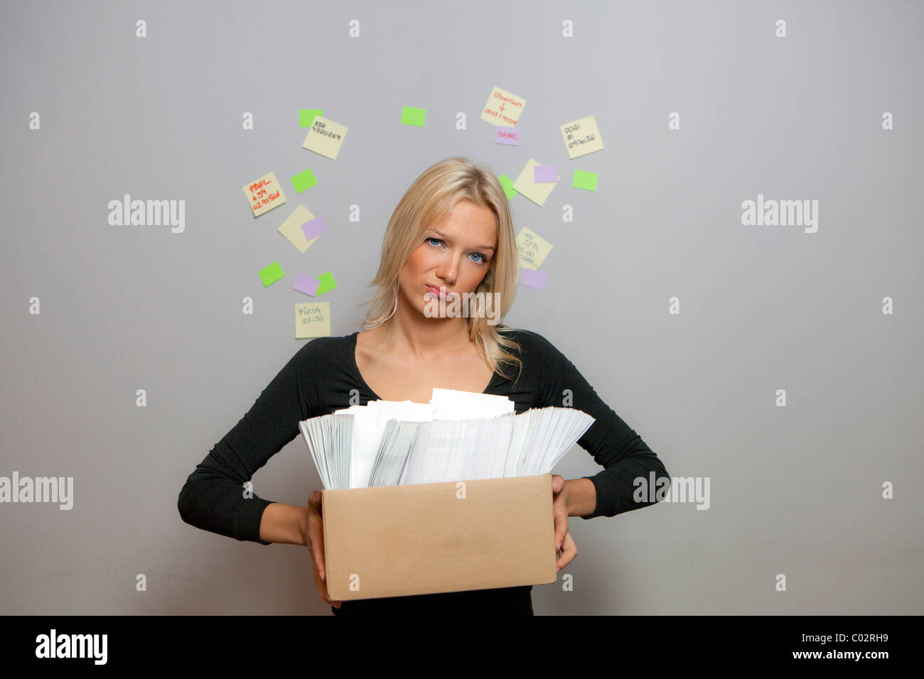 girl lifts a box of envelopes and correspondence with the post it on the wall - Stock Image