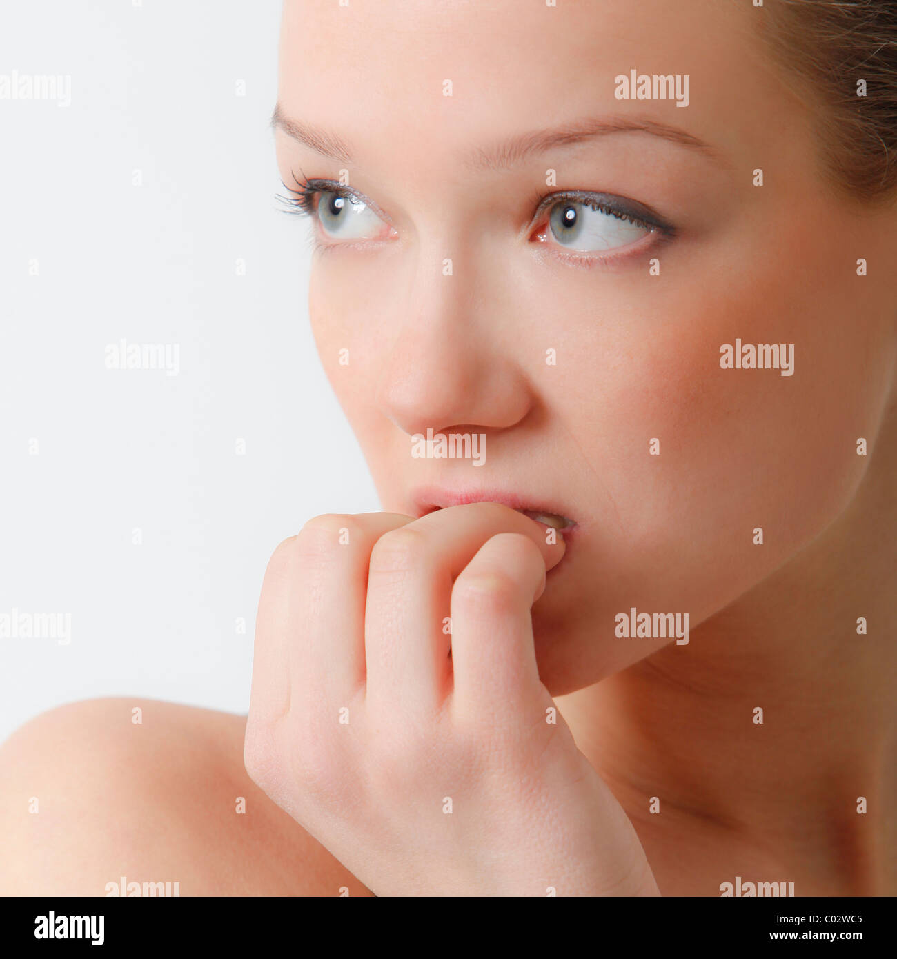 young woman biting one's nails - Stock Image