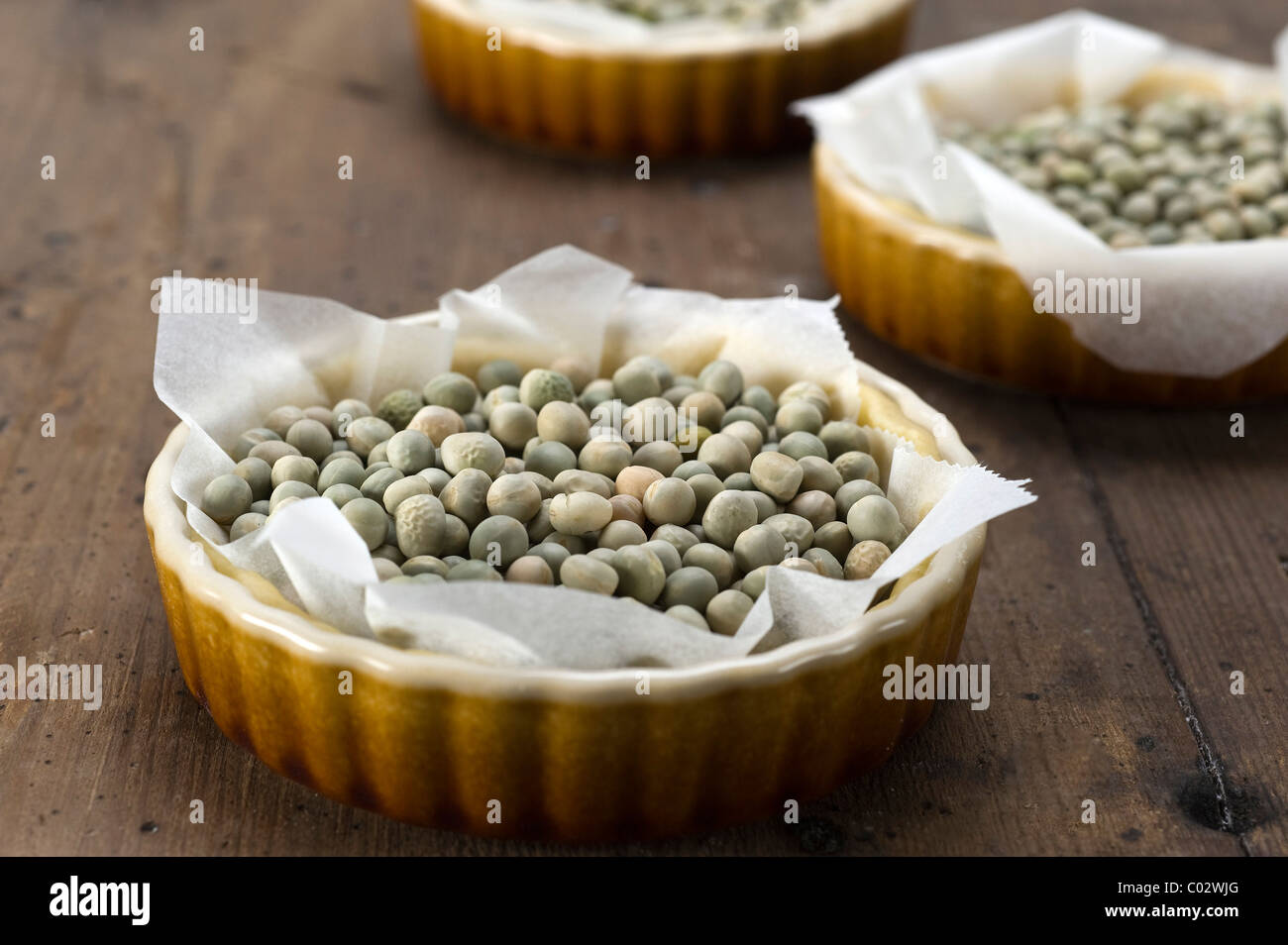 Tartlet forms with shortcrust ready for blind-baking with peas - Stock Image