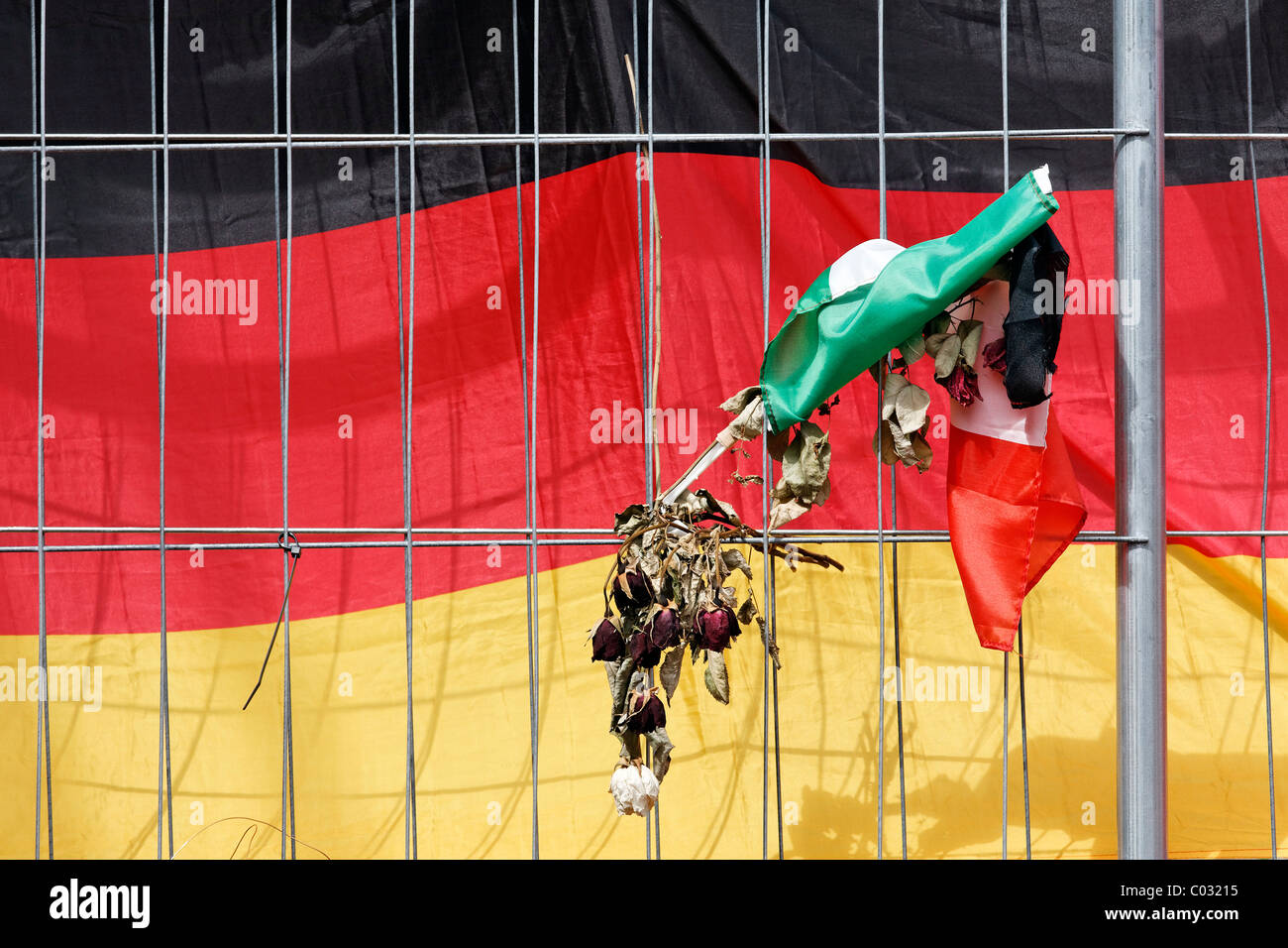 Fence with dried flower against a German flag, to remember the victims of the crowd crush at the Loveparade 2010, - Stock Image