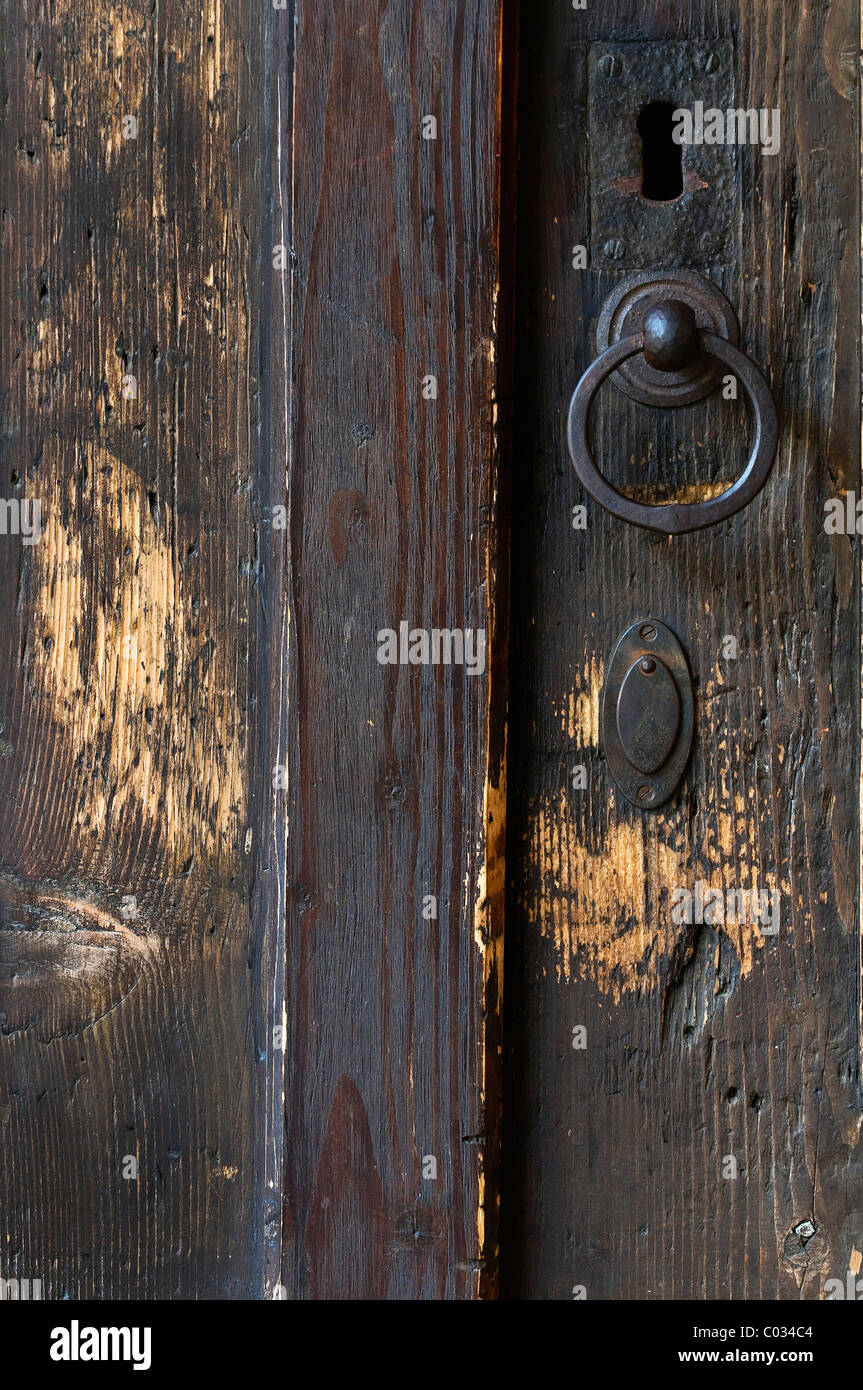 Old scratched wooden door with metal fittings, knocker and a keyhole with keyhole cover - Stock Image