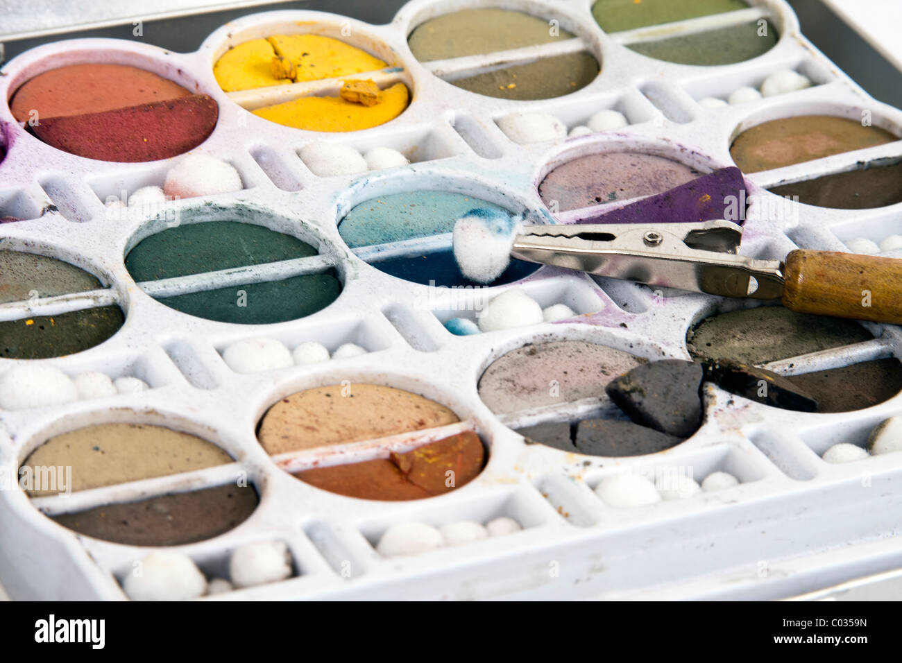 Soft earth tone chalks in their container with clip tool. - Stock Image
