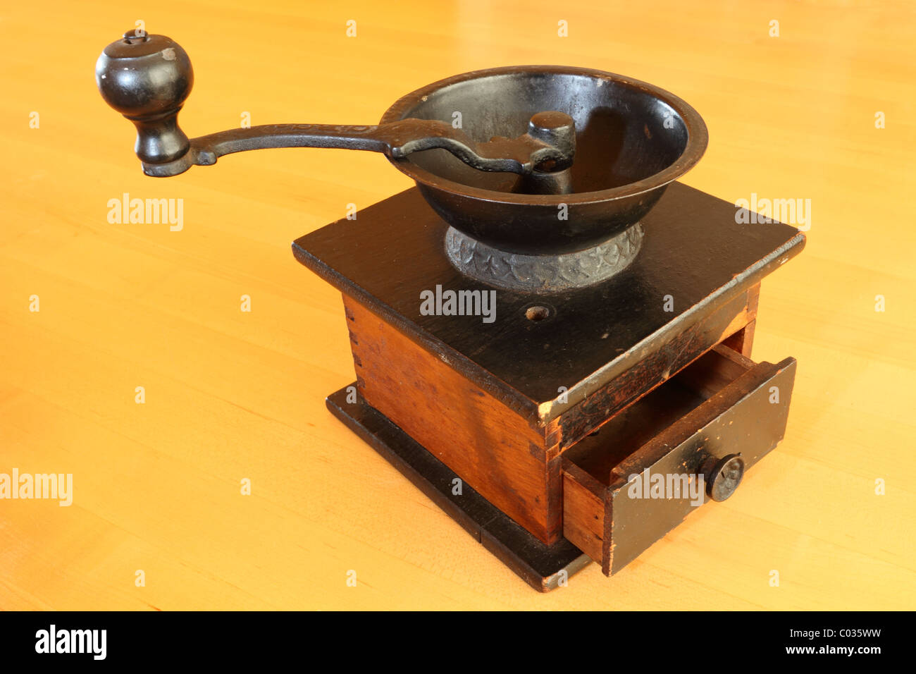 Still-life of an antique hand cranked tabletop coffee grinder. - Stock Image