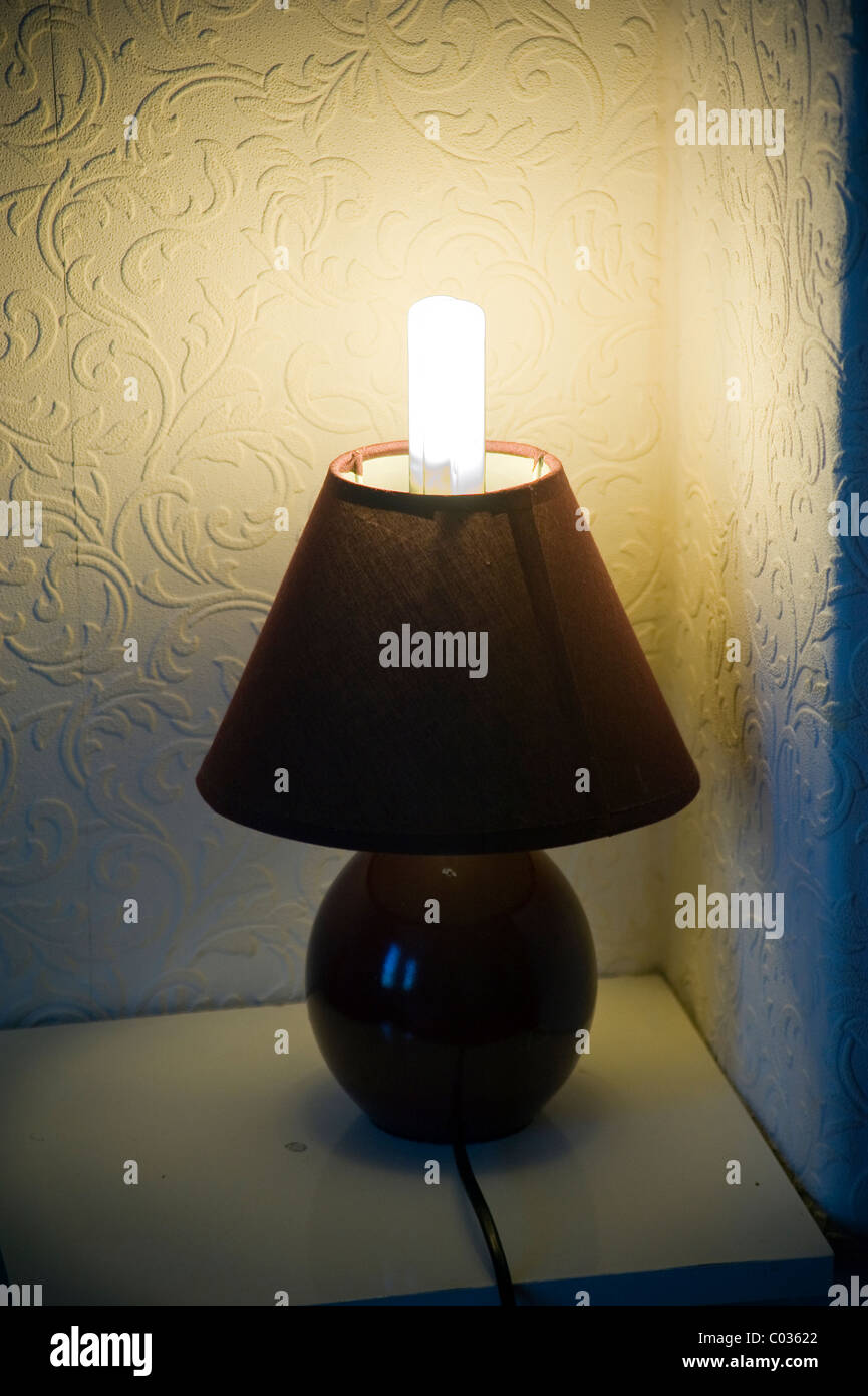 Badly fitting eco lightbulb and bedside lamp - Stock Image