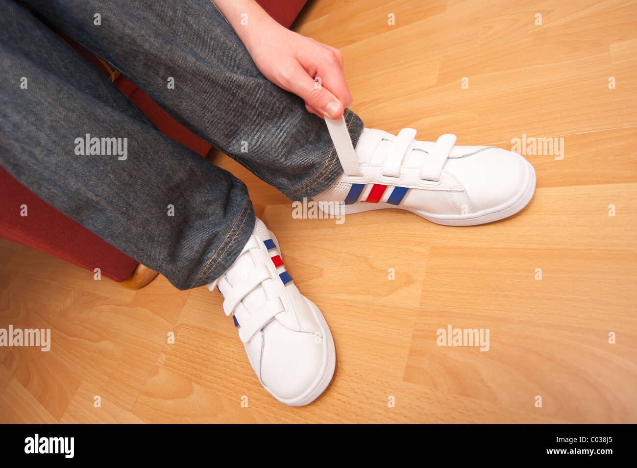 A MODEL RELEASED picture of an eleven year old boy fastening his velcro trainers in the Uk - Stock Image