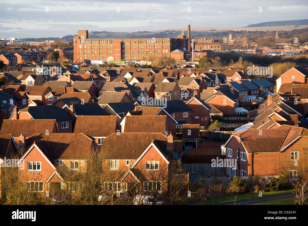 Modern housing estate and old cotton mill (Pilot Mill) with moors beyond, Bury, Greater Manchester, UK - Stock Image