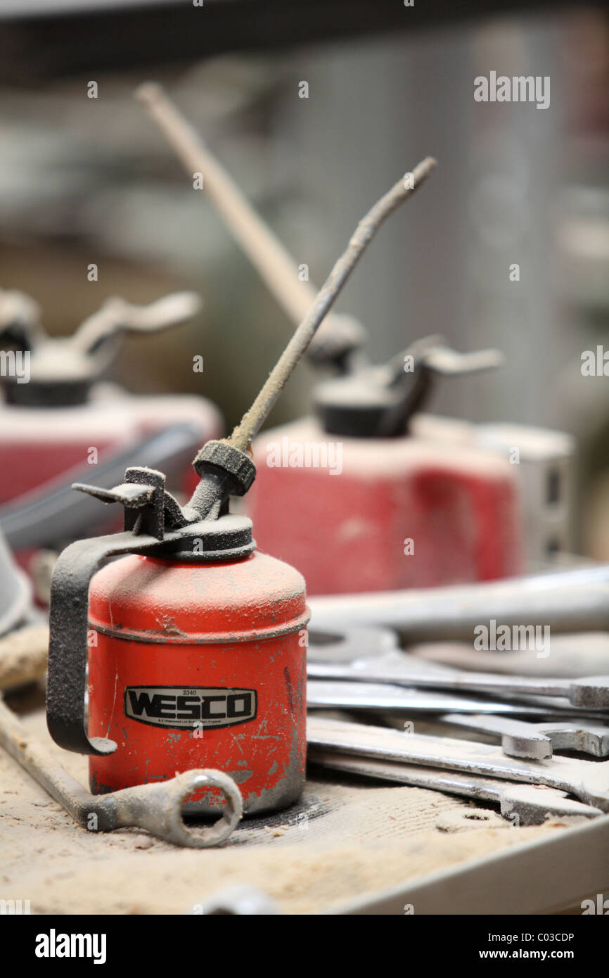 Red oil cans on dusty counter - Stock Image