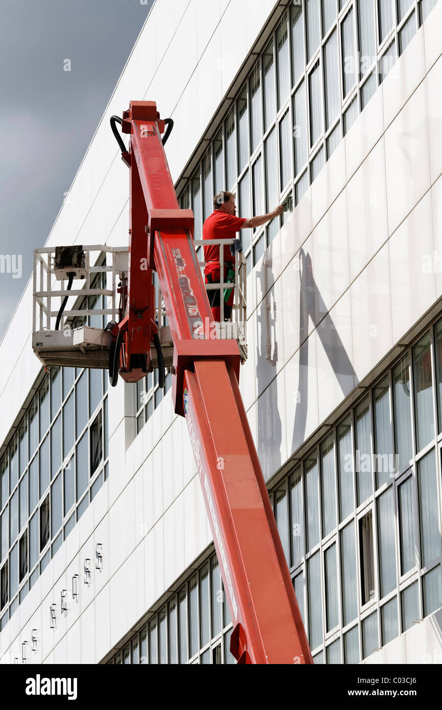 Building cleaner on a boom lift cleaning the windows of Neuss Courthouse, Lower Rhine, North Rhine-Westphalia, Germany, - Stock Image