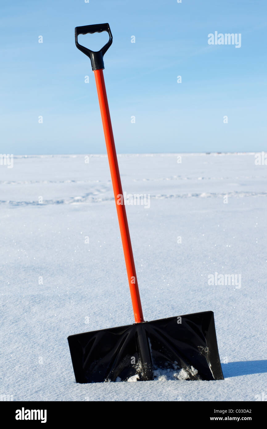 A snow shovel planted in the snow. - Stock Image